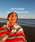 A happy Hispanic man wrapped in a serape or blanket and laughing at the beach in the evening.
